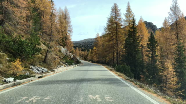 Driving through the road of the beautiful Dolomites mountains with autumn colors.