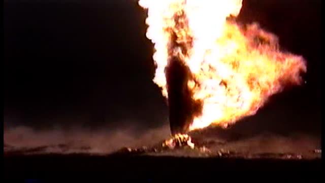 driving through the smoke of kuwaiti oil well fires set by retreating iraqi forces the smoke so black and thick making it seem like night - operation desert storm bildbanksvideor och videomaterial från bakom kulisserna