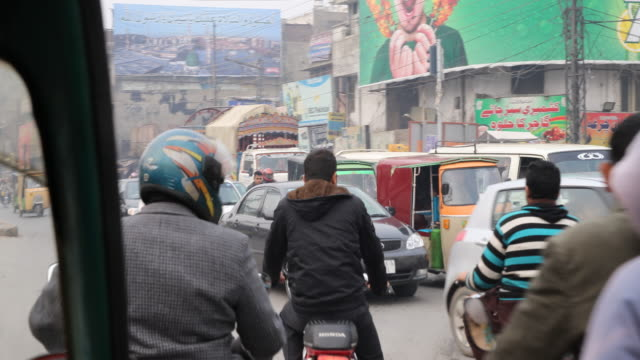 Driving through the streets of Lahore passing motorcyclists, tuk tuks, cars etc.