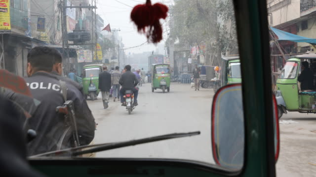 driving through the streets of lahore passing motorcyclists, tuk tuks, cars etc. - lahore pakistan stock videos & royalty-free footage