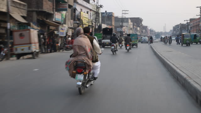 driving through the streets of lahore passing motorcyclists, tuk tuks, cars etc. - punjab pakistan stock videos and b-roll footage