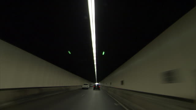 WS POV driving through tunnel and into bright sunshine / Sydney, New South Wales, Australia