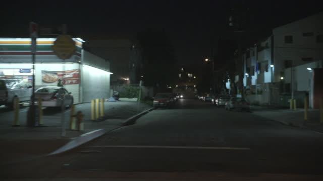 POV Driving through urban streets at night / Los Angeles, California, United States