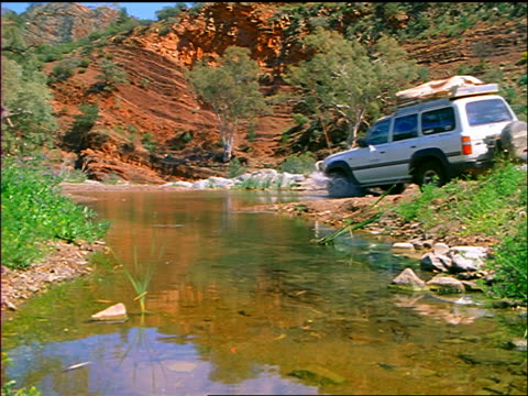 suv driving thru shallow stream / mountains in background / flinders ranges, south australia - suv点の映像素材/bロール