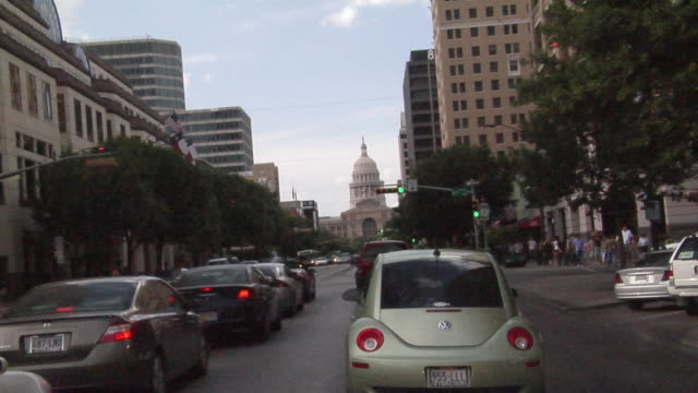 ws car pov driving toward texas state capitol building/ austin, texas - stars and stripes stock videos & royalty-free footage