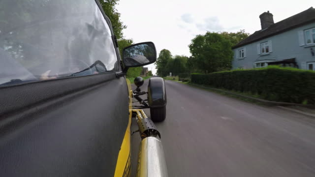 driving pov traveling along a single track road through a small hamlet in the wiltshire countryside with a view of the drivers side of a caterham seven sports car in the foreground - doppelhaus stock-videos und b-roll-filmmaterial