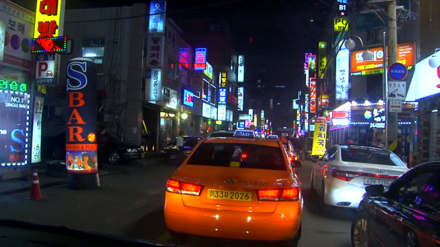 WS Driving two lane street behind taxi cab passing bars clubs cafes some neon signs bilingual English Korean lettering on most unidentifiable people...