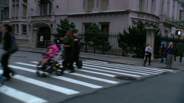 DS Driving with traffic in an Upper West Side residential area, with pedestrians on the crosswalk and a line of townhouses / New York City, New York, United States