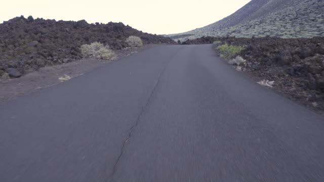 vídeos de stock, filmes e b-roll de driving/process plates. straight empty road pov. volcanic landscape with cliffs at el hierro canary islands spain. - hierro