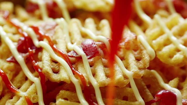 stockvideo's en b-roll-footage met drizzling ketchup on waffle fries - huishuidkunde