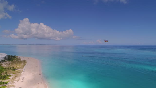 drone 4k aerial view parasailing through peferct famous awesome beach grace bay - provo stock videos and b-roll footage