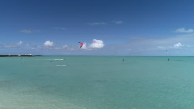 drone aerial 4k pan of kiteboarding of perfect sunny day with clear blue water - タークスとケイコス諸島点の映像素材/bロール