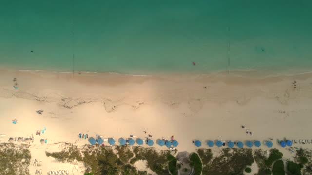 drone aerial 4k pan view of shoreline and ocean blue water - タークスとケイコス諸島点の映像素材/bロール