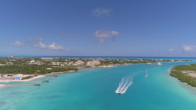 drone aerial 4k view of boat traveling past marina in turks and caicos - provo stock videos and b-roll footage