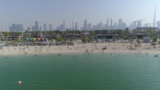 Drone aerial along La Mer beach with Dubai skyline in background