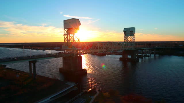 vídeos de stock, filmes e b-roll de wide drone aerial cape fear memorial bridge over cape fear river at sunset - wilmington carolina do norte