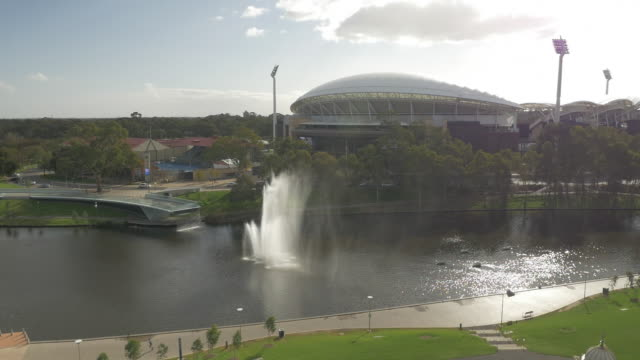 drone aerial circling torrens river fountain to see adelaide oval exterior in background - adelaide river stock videos & royalty-free footage