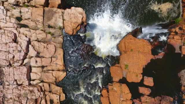 vídeos y material grabado en eventos de stock de drone aerial close up overhead aerial view looking straight down a waterfall in the berkeley river gorge track back along the creek feeding the... - red rocks