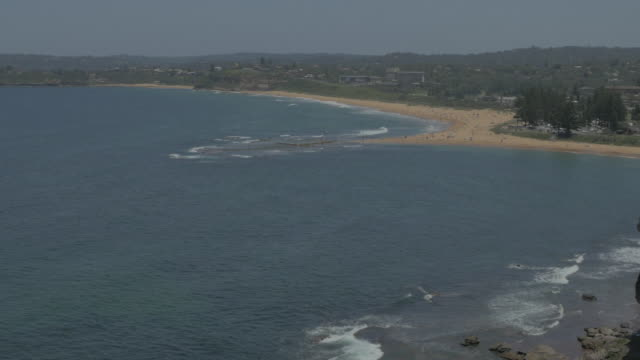 drone aerial coastline around mona vale beach track to view over headland looking south to turimetta head - felswand stock-videos und b-roll-filmmaterial