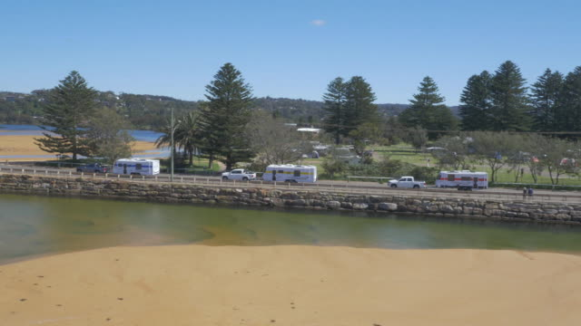 drone aerial convoy of three utes towing caravans passes in front of lakeside caravan park and over south creek bridge narrabeen - camper van stock videos & royalty-free footage