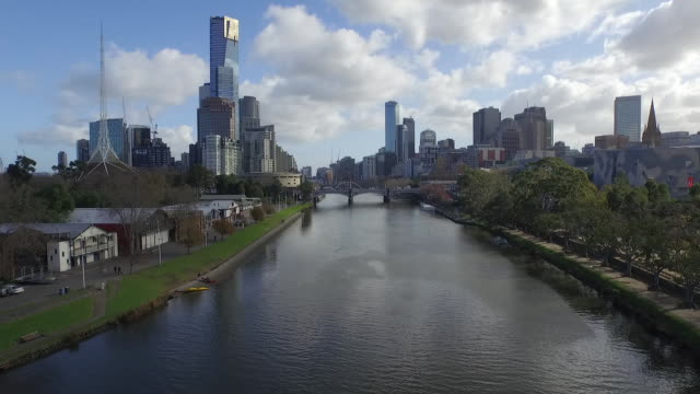 drone aerial day along the yarra river towards the city with rowing club boatsheds on the left over the princes bridge with trams and traffic... - ウォータースポーツ点の映像素材/bロール