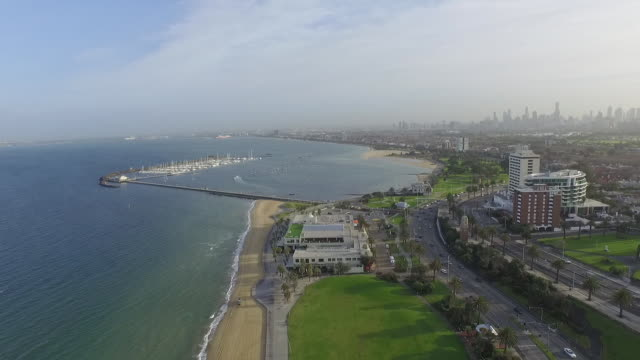 Drone Aerial Day looking north towards St Kilda Pier and Harbour Marina pan over sea baths towards Melbourne city skyline and St Kilda suburb Hazy day