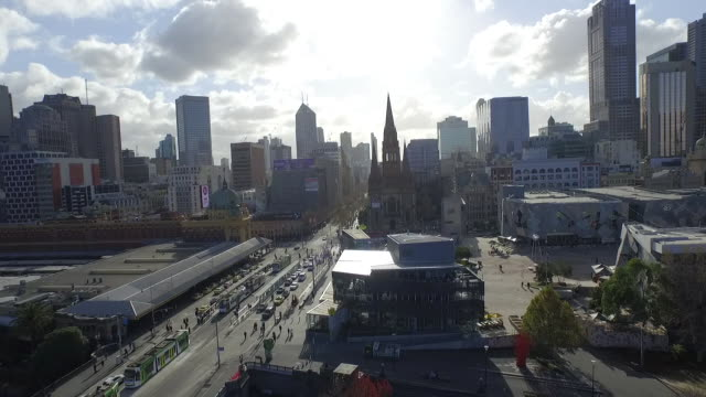 Drone Aerial Day low angle looking north to city skyline Flinders Street Station and tram stops and Federation Square in foreground St Paul's...
