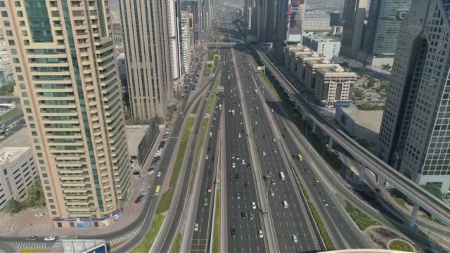 Drone aerial E11 Sheikh Zayed Road surrounded by skyscrapers running through centre of Dubai