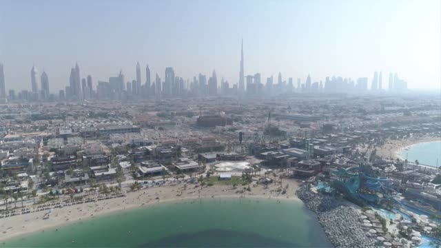 drone aerial flying away over city and la mer beach and coastline with dubai skyline in background - coastal feature stock videos & royalty-free footage