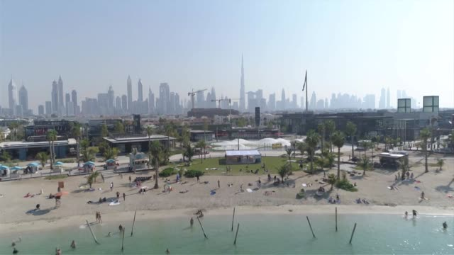 Drone aerial flying towards and away from La Mer beach with Dubai skyline in background