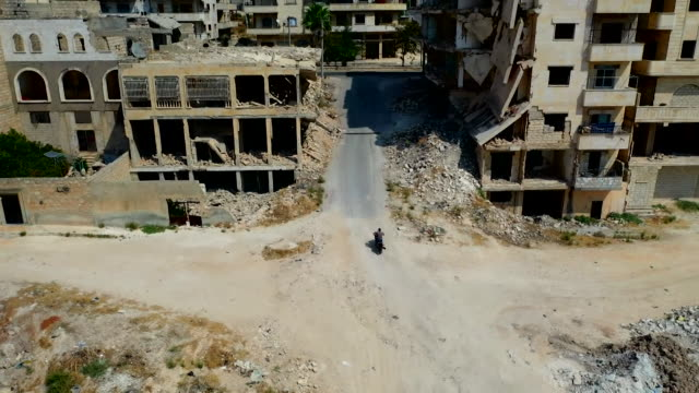 drone aerial following nurse travelling to work on motorbike to underground hospital to escape airstrikes from syrian government in rebel controlled... - destruction stock videos & royalty-free footage