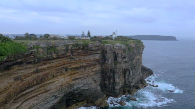 drone aerial marine rescue port jackson building zoom out / sandstone cliffs and rocks / north head in the background / tracking past watsons bay... - 堆積岩点の映像素材/bロール