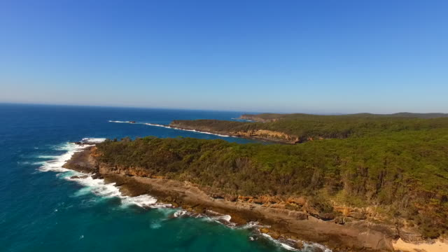 Drone aerial Murramarang Beach deserted beach with clear blue skies and calm turquoise water lapping on the yellow sand camera rises up above and...