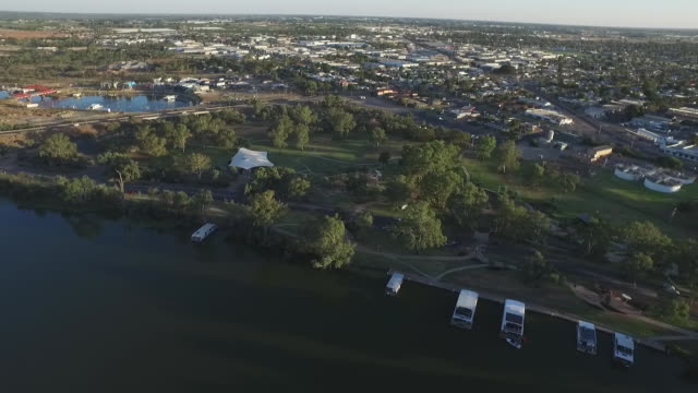 drone aerial murray river and sturt highway bridge houseboats moored along riverbank pan to riverside reserve park with mildura town in background... - flussufer stock-videos und b-roll-filmmaterial