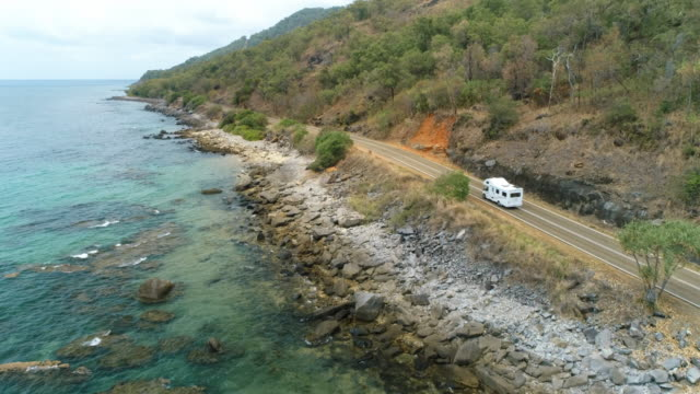 drone aerial of campervan tracking along a coast troad - camper van stock videos & royalty-free footage