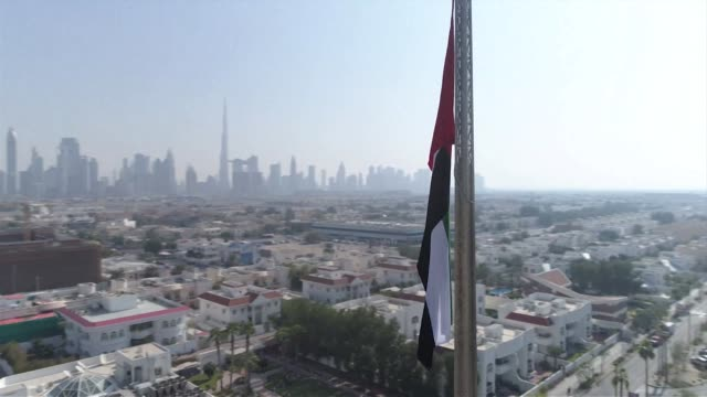 Drone aerial of Dubai city and skyline with Dubai flag in foreground