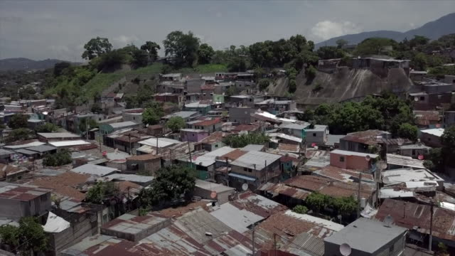 vídeos y material grabado en eventos de stock de drone aerial over built up residential area in san salvador shows the poverty that exists in the area - américa central