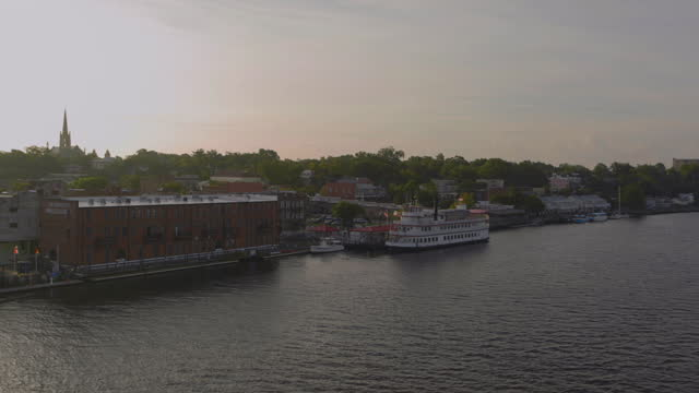 drone aerial pov over cape fear river with pan to riverwalk on downtown wilmington waterfront in morning - wilmington north carolina stock-videos und b-roll-filmmaterial