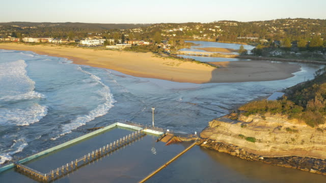 drone aerial over north narrabeen rockpool ocean baths zoom over south creek estuary and lakeside holiday park - gezeitentümpel stock-videos und b-roll-filmmaterial