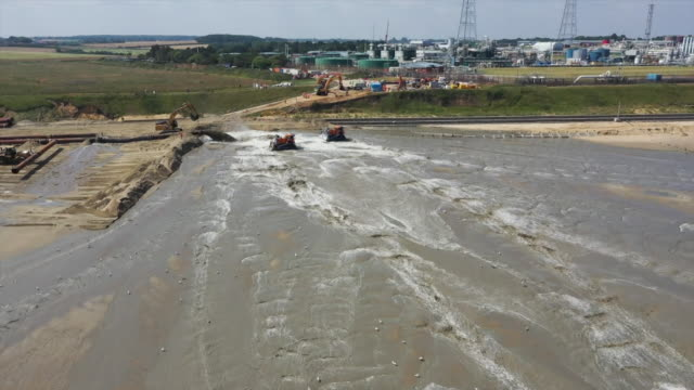 vidéos et rushes de drone aerial over sea, beach, diggers and bacton gas terminal, where a sandscaping project is in operation, where sand is pumped onto a beach to... - érodé