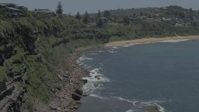 vídeos de stock e filmes b-roll de drone aerial pan headland cliffs towards bungan beach homes bush and bungan head - paredão rochoso