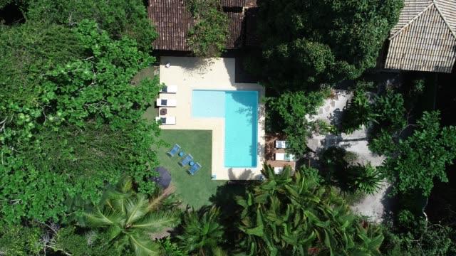 vídeos de stock, filmes e b-roll de zangão aéreo ponto de vista a descer para a piscina do hotel de luxo - cena rural