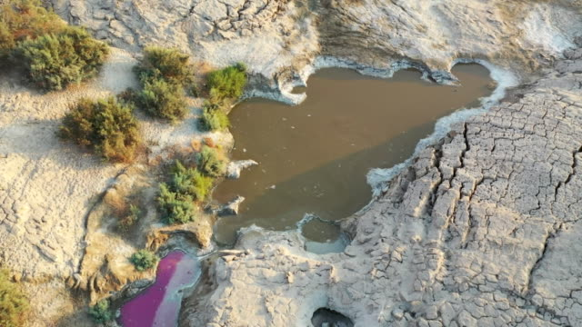 drone aerial pools of water amongst arid land affected by drought and climate change, jordan - land stock videos & royalty-free footage