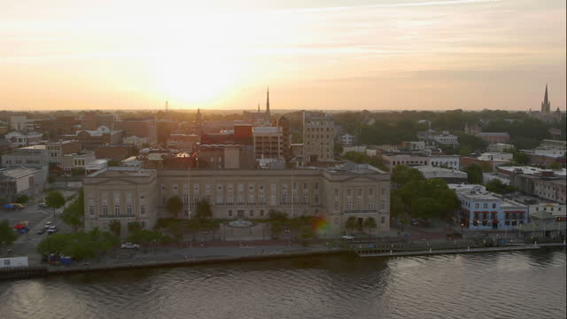 drone aerial rear pov from downtown wilmington over alton lennon federal building on downtown wilmington waterfront on cape fear river at sunrise - wilmington north carolina stock-videos und b-roll-filmmaterial