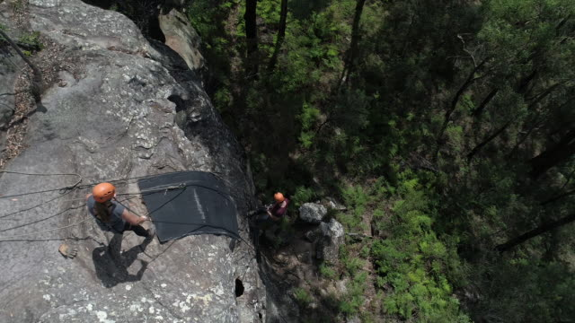 vídeos de stock e filmes b-roll de drone aerial several abseilers preparing their ropes and safety equipment on a rock face camera pans back to the surrounding bushland and valleys and... - corda de trepar