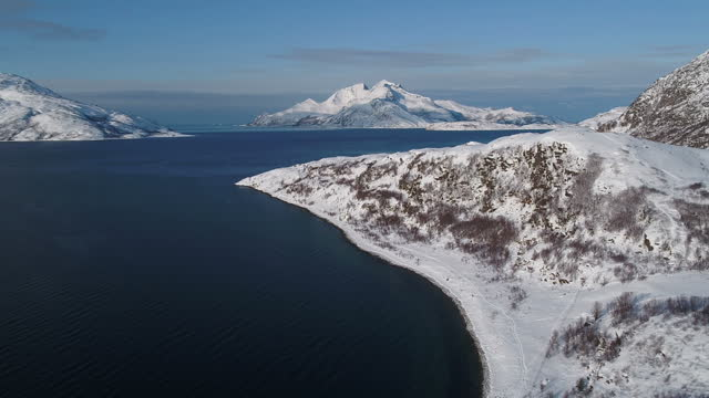 drone aerial shots of a village and snowcovered landscape on the edge of a fjord near tromso on march 09 2017 in tromso norway - landscape scenery点の映像素材/bロール