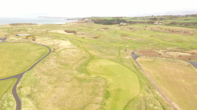 drone aerial shots of an empty closed royal portrush golf course and empty beach on an overcast day during the coronavirus lockdown on 13 may 2020 in... - overcast stock videos & royalty-free footage