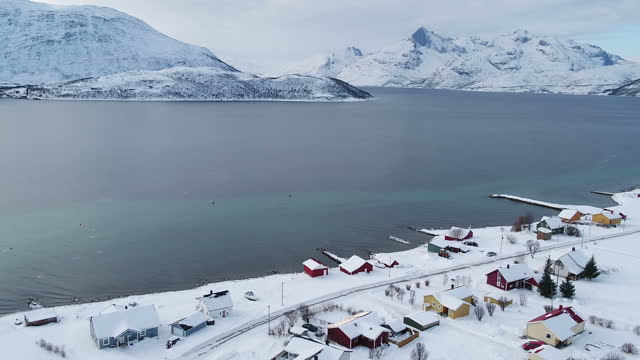 drone aerial shots of the landscape on the outskirts of tromso with wooden houses next to a fjord and snow covered mountains in the distance on march... - landscape scenery点の映像素材/bロール