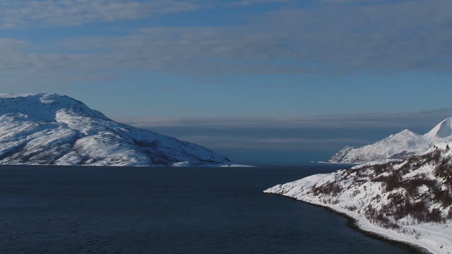 drone aerial shots of the snowcovered landscape near tromso including a village at the mouth of a fjord and a group of reindeer grazing with... - landscape scenery点の映像素材/bロール