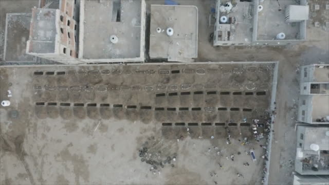 drone aerial shots over mass graves of suspected coronavirus victims as a burial takes place on 17 may 2020 in aden, yemen - yemen bildbanksvideor och videomaterial från bakom kulisserna